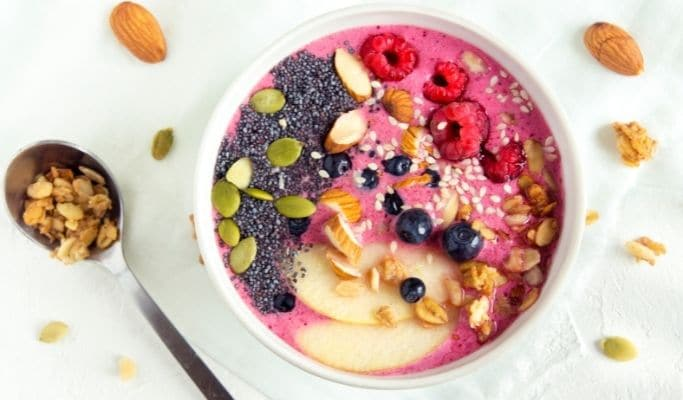 red smoothie bowl topped with berries, seeds, and more